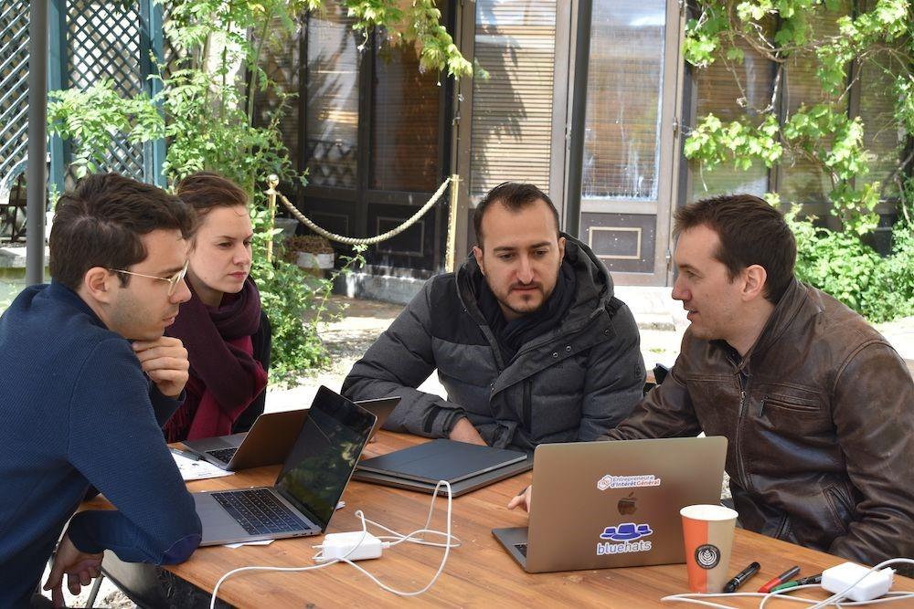 Une femme et trois hommes sont assis autour d'une table, en l'extérieur, sur laquelle on voit plusieurs ordinateurs. Ils discutent en regardant quelque chose sur un des ordinateurs.